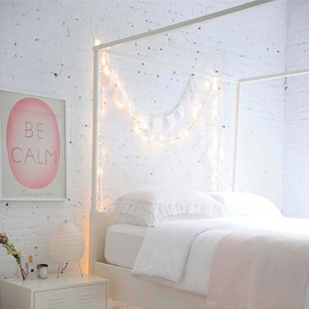 using string lights to add interest to white bedroom walls