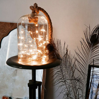 a lamp of string lights stuffed into a glass container