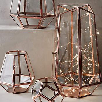 a lamp of string lights stuffed into a geometric container